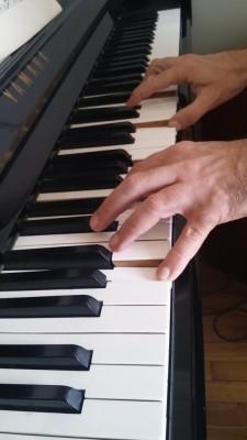 Mains de Patrick Issarni, professeur de piano, sur le clavier de son piano